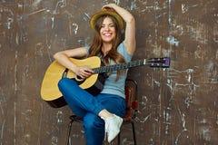 Mujer joven que se sienta con la guitarra en fondo de la pared del grunge Foto de archivo libre de regalías
