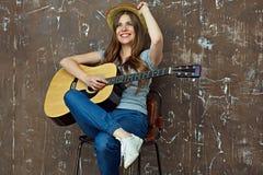 Mujer joven que se sienta con la guitarra en fondo de la pared del grunge Fotografía de archivo libre de regalías