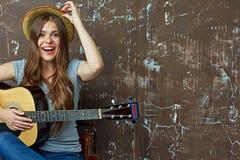 Mujer joven que se sienta con la guitarra en fondo de la pared del grunge Imagen de archivo