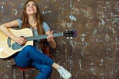 Mujer joven que se sienta con la guitarra en fondo de la pared del grunge Imagenes de archivo