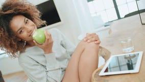 Mujer joven que se sienta con la manzana verde en casa y que sonríe en la cámara almacen de video