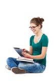 Mujer joven que se sienta con la tableta digital Imagen de archivo libre de regalías