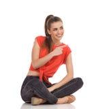 Mujer joven que se sienta con las piernas cruzadas y señalar Imagen de archivo