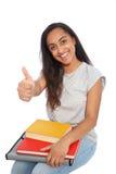 Mujer joven que se sienta con los libros que muestran los pulgares para arriba Fotografía de archivo libre de regalías