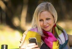 Mujer joven que se sienta con smartphone Fotos de archivo