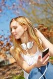 Mujer joven que se sienta con smartphone en parque Fotografía de archivo