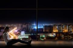 Mujer joven que se sienta con un ordenador portátil por la ventana Imágenes de archivo libres de regalías
