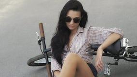 Mujer joven que se sienta con una bicicleta al aire libre almacen de video
