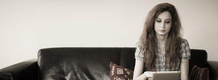 Mujer joven que se sienta con una tableta en un sofá Fotografía de archivo