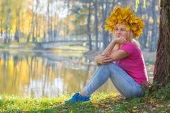 Mujer joven que se sienta debajo del árbol Fotografía de archivo libre de regalías