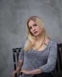 Mujer joven que se sienta delante del muro de cemento gris Fotos de archivo libres de regalías