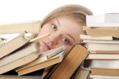 Mujer joven que se sienta detrás de los libros Foto de archivo libre de regalías