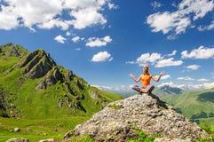 Mujer joven que se sienta en actitud de la yoga en montañas Foto de archivo libre de regalías