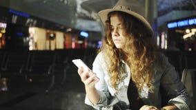 Mujer joven que se sienta en aeropuerto metrajes