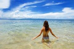 Mujer joven que se sienta en agua clara en la isla de Taveuni, Fiji foto de archivo libre de regalías