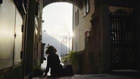Mujer joven que se sienta en arco almacen de metraje de vídeo