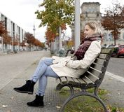 Mujer joven que se sienta en banco Imagen de archivo