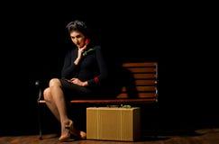 Mujer joven que se sienta en banco Foto de archivo libre de regalías