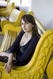 Mujer joven que se sienta en banco amarillo Fotografía de archivo libre de regalías