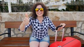 Mujer joven que se sienta en banco con la maleta almacen de video