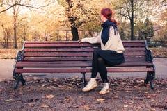 Mujer joven que se sienta en banco de parque Fotos de archivo