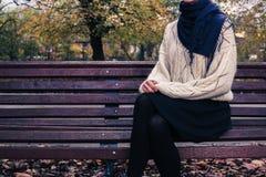 Mujer joven que se sienta en banco de parque Imagen de archivo libre de regalías