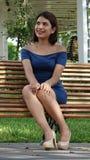 Mujer joven que se sienta en banco de parque Imágenes de archivo libres de regalías