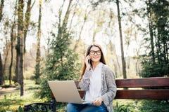 Mujer joven que se sienta en banco en el parque que habla en el teléfono celular y que usa el ordenador portátil Fotografía de archivo