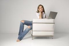 Mujer joven que se sienta en butaca con la computadora portátil Fotografía de archivo libre de regalías
