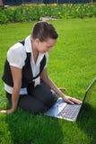 Mujer joven que se sienta en césped con la computadora portátil Fotos de archivo