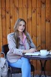 Mujer joven que se sienta en café con café Imagen de archivo