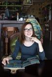Mujer joven que se sienta en café con el menú Fotografía de archivo