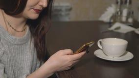 Mujer joven que se sienta en café con el teléfono y el té de consumición almacen de metraje de vídeo