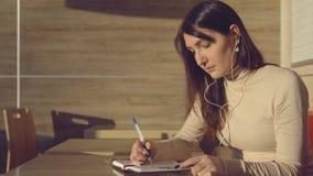 Mujer joven que se sienta en café con los auriculares y que hace notas en cuaderno almacen de metraje de vídeo
