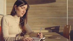 Mujer joven que se sienta en café con los auriculares y que hace notas en cuaderno imagen de archivo libre de regalías