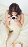 Mujer joven que se sienta en café de consumición de la cama imágenes de archivo libres de regalías