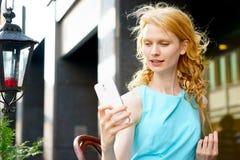 Mujer joven que se sienta en café y que usa smartphone blanco moderno Imágenes de archivo libres de regalías