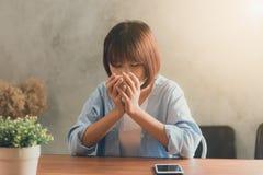Mujer joven que se sienta en cafetería en la tabla de madera, el café de consumición y usando smartphone Imagen de archivo