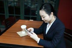 Mujer joven que se sienta en cafetería en la tabla de madera, el café de consumición y usando smartphone En la tabla es el ordena fotografía de archivo libre de regalías