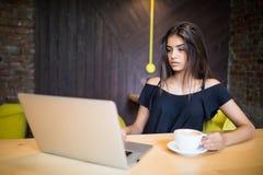 Mujer joven que se sienta en cafetería en la tabla de madera, el café de consumición y usando smartphone En la tabla es el ordena foto de archivo