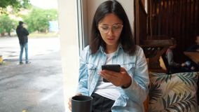 Mujer joven que se sienta en cafeter?a Internet de la ojeada de la muchacha, charlando, blogging Teléfono que se sostiene femenin metrajes