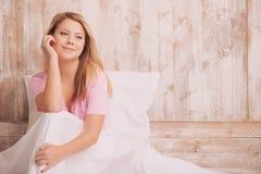Mujer joven que se sienta en cama y cara conmovedora Foto de archivo libre de regalías