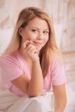 Mujer joven que se sienta en cama y cara conmovedora Fotografía de archivo