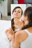 Mujer joven que se sienta en cama y que mira en el espejo Fotos de archivo