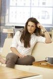 Mujer joven que se sienta en casa en el sofá Imágenes de archivo libres de regalías