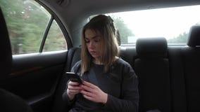 Mujer joven que se sienta en el asiento trasero de un coche, enfocado almacen de metraje de vídeo