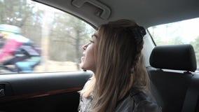 Mujer joven que se sienta en el asiento trasero de un coche metrajes