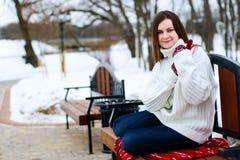 Mujer joven que se sienta en el banco Fotografía de archivo
