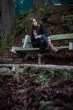 Mujer joven que se sienta en el banco Imagen de archivo