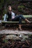 Mujer joven que se sienta en el banco en bosque Fotografía de archivo libre de regalías